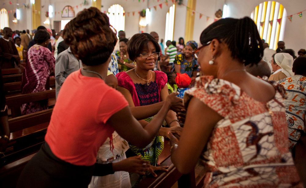 . Churchgoers wish each other a happy new year at the Notre Dame Cathedral of the Immaculate Conception in Bangui, Central African Republic, Tuesday, Jan. 1, 2013. President Francois Bozize\'s government is coming under growing threat as rebels vowing to overthrow him rejected appeals from the African Union to hold their advance and try to form a coalition government. (AP Photo/Ben Curtis)