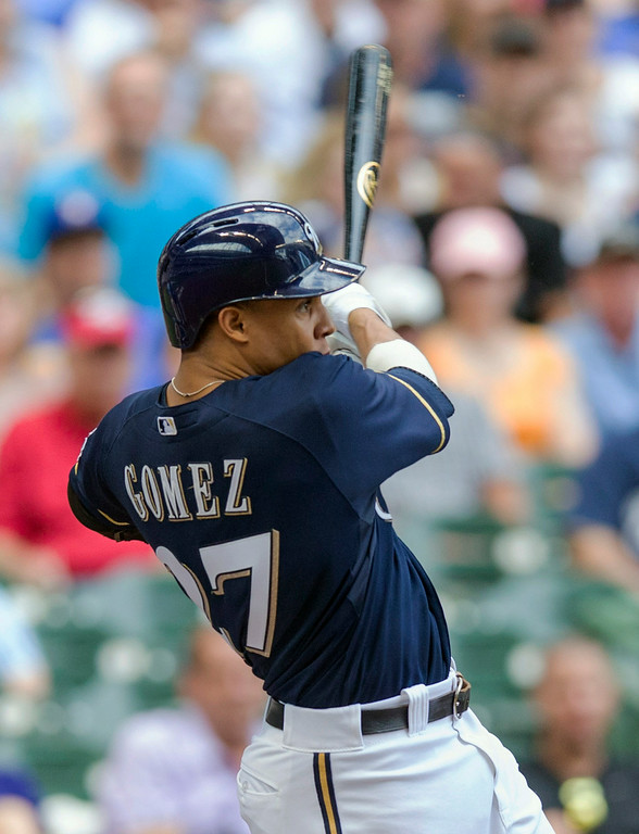 . Carlos Gomez of the Milwaukee Brewers follows through on a two-run home run off of Jhoulys Chacin of the Colorado Rockies\' during the first inning of a baseball game Saturday, June 28, 2014, in Milwaukee. (AP Photo/Tom Lynn)