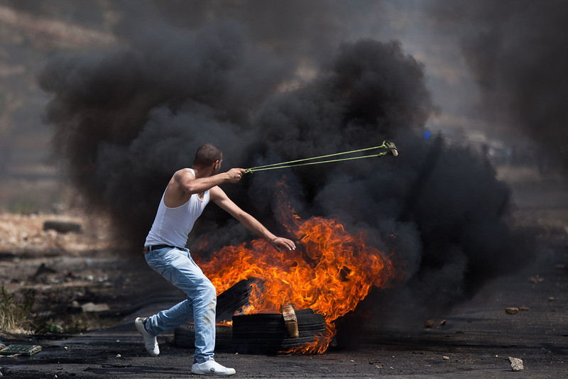 ". A Palestinian demonstrator throws a stone toward Israeli soldiers during clashes outside of Ofer Prison on May 15, 2012 near the West Bank city of Ramallah. Palestinians mark Israel\'s establishment in 1948 with ""Nakba\"" or \""catastrophe\"" day on May 15, to remember the thousands of Palestinians who fled or were expelled during the creation of the Jewish state and the subsequent war.  (Photo by Uriel Sinai/Getty Images)"