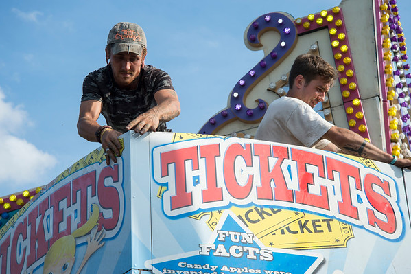09/11/19 Wesley Bunnell | StaffrrCarnival workers assemble attractions ahead of the Berlin Fair taking place this weekend. Jeremiah Delorme, L, Braxton Claire stand on top of a ticket booth as they complete the set up.