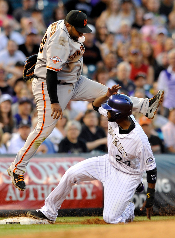 . Colorado Rockies\' Dexter Fowler (24) is safe at third after a throwing error by Angel Pagan to San Francisco Giants third baseman Pablo Sandoval (48) during the third inning of a baseball game on Friday, May 17, 2013, in Denver. Fowler scored on the play. (AP Photo/Jack Dempsey)