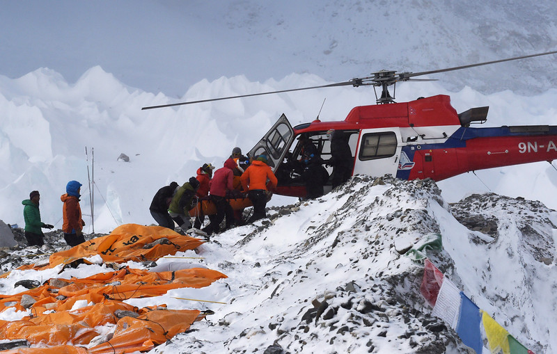 . An injured person is loaded onto a rescue helicopter at Everest Base Camp on April 26, 2015, a day after an avalanche triggered by an earthquake devastated the camp. Rescuers in Nepal are searching frantically for survivors of a huge quake on April 25, that killed nearly 2,000, digging through rubble in the devastated capital Kathmandu and airlifting victims of an avalanche at Everest base Camp. The bodies of those who perished lie under orange tents. ROBERTO SCHMIDT/AFP/Getty Images