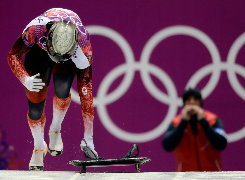. Eric Neilson of Canada starts his second run as a coach cheers behind him, during the men\'s skeleton competition at the 2014 Winter Olympics, Friday, Feb. 14, 2014, in Krasnaya Polyana, Russia. (AP Photo/Natacha Pisarenko)