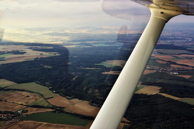 Pohled směrem k Jeseníkům a Litovli. Víska vpravo s těmi třemi bílými halami je Vilémov.