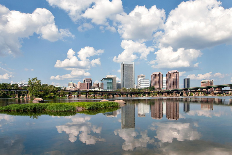 Clouds and a blue sky reflect in the James River near high rise buildings in Richmond, VA