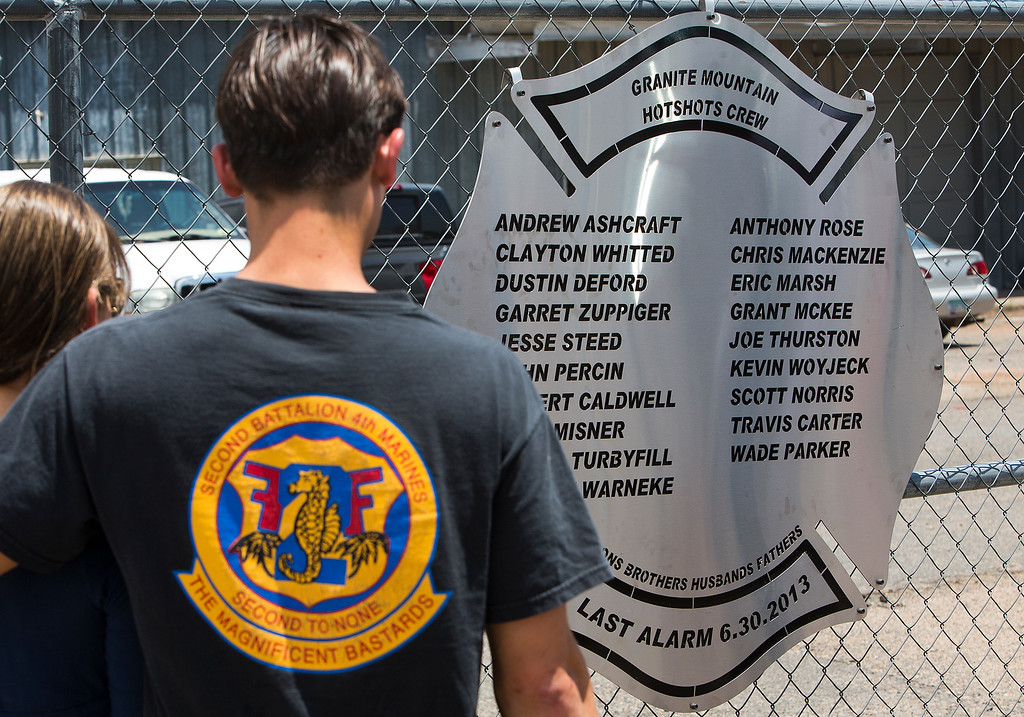 . A plaque is posted on a fence outside Fire Station 7 in Prescott, Ariz. on Tuesday, July 2, 2013 in a makeshift memorial for the 19 Granite Mountain Hotshots who were killed by an out-of-control blaze near Yarnell, Ariz. on Sunday. (AP Photo/The Arizona Republic, Tom Tingle)