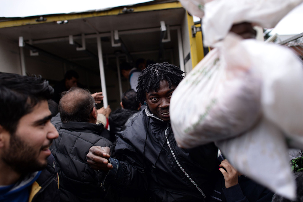 . A man receives a bag of meat as refugees push each other during a food distribution by Bulgaria\'s chief mufti to mark the Muslim holiday of Eid al-Adha at a refugee centre in Sofia on October 17, 2013. Bulgaria said it plans to build a fence on its southeastern border with Turkey to limit the number of illegal Syrian immigrants entering the country and creating a refugee crisis. DIMITAR DILKOFF/AFP/Getty Images