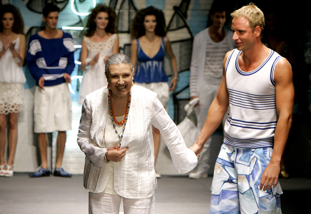 . FILE - In this June 27, 2006 file photo, Italian designer Laura Biagiotti, left, acknowledges the audience\'s applause as she holds hands with Italian world swimming champion Massimiliano Rosolino, at the end of her Laura Biagiotti Spring-Summer 2007 men\'s collection, unveiled during the men\'s Fashion Week in Milan, Italy. Biagiotti died May 26 at age 73. (AP Photo/Antonio Calanni, files)