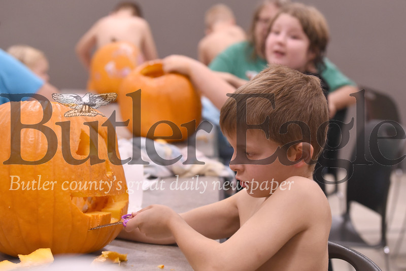 Lennon Grossbauer, 8, of Butler carves his pumpkin at the Butler YMCA Saturday. Seb Foltz/Butler Eagle