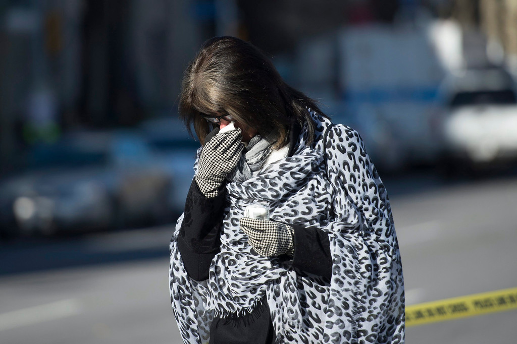 . A woman leaves after paying her respects to Cpl. Nathan Cirillo, 24,  at the National War Memorial in Ottawa, near Parliament Hill on Thursday, Oct. 23, 2014.  Michael Zehaf Bibeau fatally shot  Cirillo on Wednesday, at the National War Memorial before setting his sights on Parliament Hill. Bibeau was killed just feet from where hundreds of MPs were meeting for their weekly caucus meetings.  (AP Photo/The Canadian Press, Justin Tang)