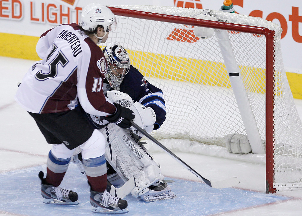 . Colorado Avalanche\'s PA Parenteau (15) scores on his penalty shot on Winnipeg Jets goaltender Ondrej Pavelec (31) for the win in an NHL hockey game, Thursday, Dec. 12, 2013 in Winnipeg, Manitoba. (AP Photo/The Canadian Press, John Woods)