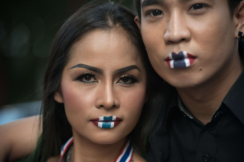 """. Thai anti-government protesters with national flag painted on their lips pose for a photograph at Ratchaprasong intersection during a rally in Bangkok on January 13, 2014. Thai opposition protesters launched their attempted \""""shutdown\"""" of Bangkok on January 13, occupying key intersections in the capital in an escalation of their campaign to unseat Prime Minister Yingluck Shinawatra. (NICOLAS ASFOURI/AFP/Getty Images)"""