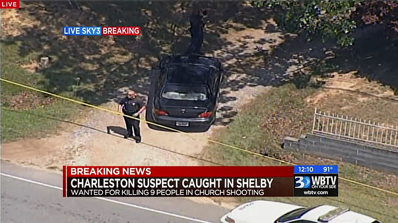 . In this image taken from video and released by WBTV, police stand near the vehicle that was driven by Dylann Storm Roof, Thursday, June 18, 2015, in Shelby, N.C. Roof, 21, was arrested Thursday in the slayings of nine people, including the pastor, at a prayer meeting inside a historic black church in downtown Charleston. (WBTV via AP)