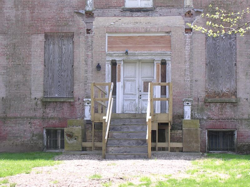 Once, this house was a a handsome mansion with a graceful porch, black shutters, and glowing pink bricks. Now the windows are boarded, temporary steps go up to the door, and the bricks are covered with dirt and moss. But the house still emanates a faded grandeur.