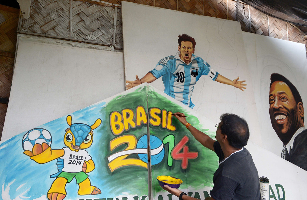 . An Indian artist gives finishing touches to a poster of Argentine soccer player Lionel Messi (L) and Brazilian soccer legend Pele at a local football club in Kolkata on June 10, 2014.   Football fans in the eastern Indian city are gearing up for the upcoming Brazil FIFA World Cup 2014 and decorating their clubs with football-related paraphernalia.  AFP PHOTO/ Dibyangshu SARKAR/AFP/Getty Images