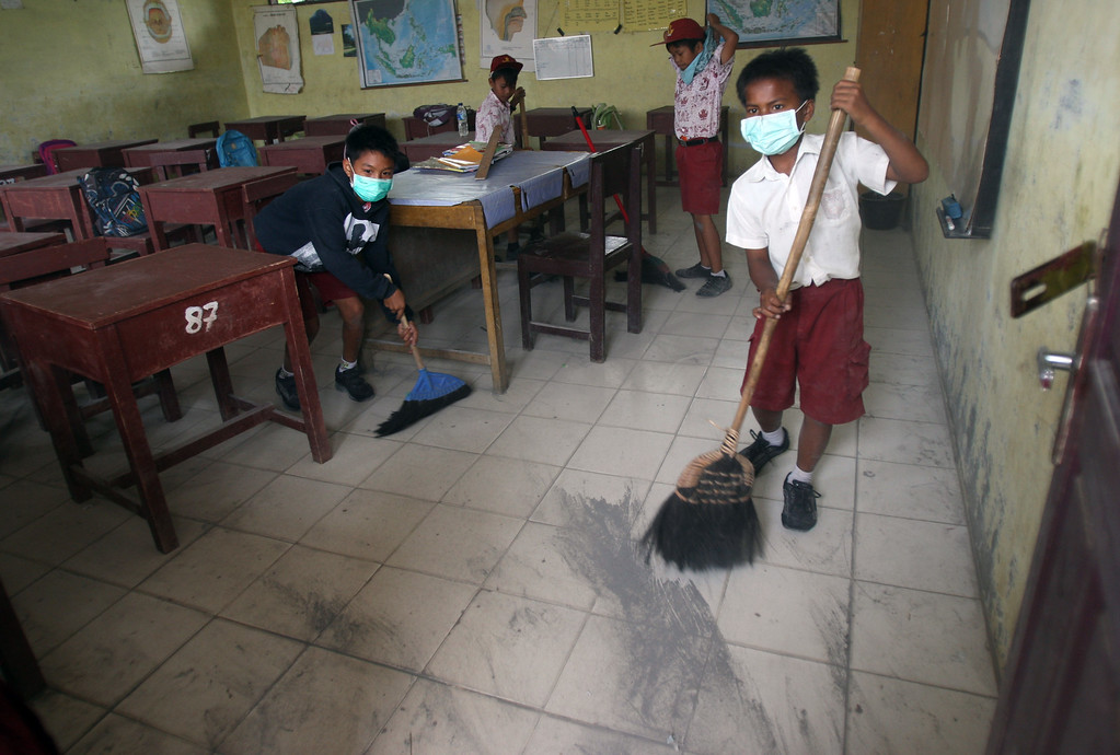 . Students sweep volcanic ash from the eruption of Mount Sinabung off the floor of their class room at an elementary school in Tiga Nderket, North Sumatra, Indonesia, Wednesday, Nov. 6, 2013. The 2,600-meter (8,530-foot) -high volcano has been erupting since Sunday, unleashing volcanic ash high into the sky and forcing the evacuation of villagers living around its slope. (AP Photo/Binsar Bakkara)
