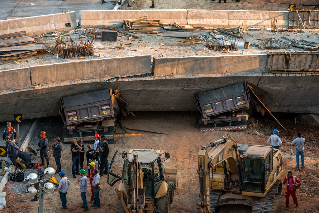 . Firefighters and policemen work at the site where several vehicles were crushed by a viaduct that collapsed in Belo Horizonte, Brazil, on July 3, 2014. An unfinished overpass collapsed on vehicles in Brazil\'s southeastern World Cup city of Belo Horizonte on Thursday, killing at least two people and injuring 19, officials said. AFP PHOTO/PEDRO DUARTE/AFP/Getty Images