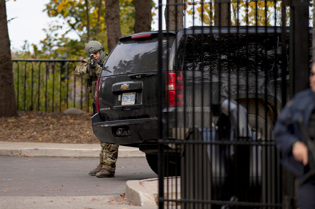 . A heavily armed RCMP officer takes position at the gate of 24 Sussex Dr., the official residence of the Prime Minister, on Wednesday, Oct. 22, 2014.  A soldier standing guard at the National War Memorial has been shot by an unknown gunman and there have been reports of gunfire inside the halls of Parliament. (AP Photo/The Canadian Press, Justin Tang)