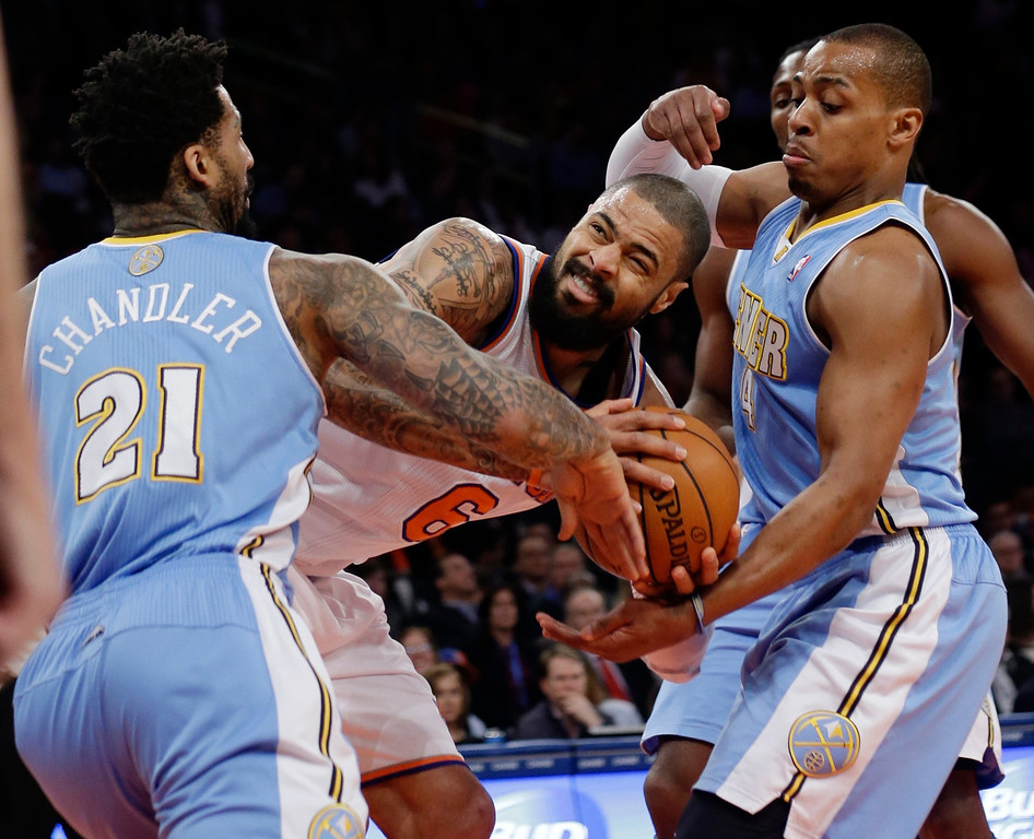 . Denver Nuggets\' Wilson Chandler (21) and Randy Foye (4) fight for control of the ball with New York Knicks\' Tyson Chandler (6) during the first half of an NBA basketball game Friday, Feb. 7, 2014, in New York. (AP Photo/Frank Franklin II)