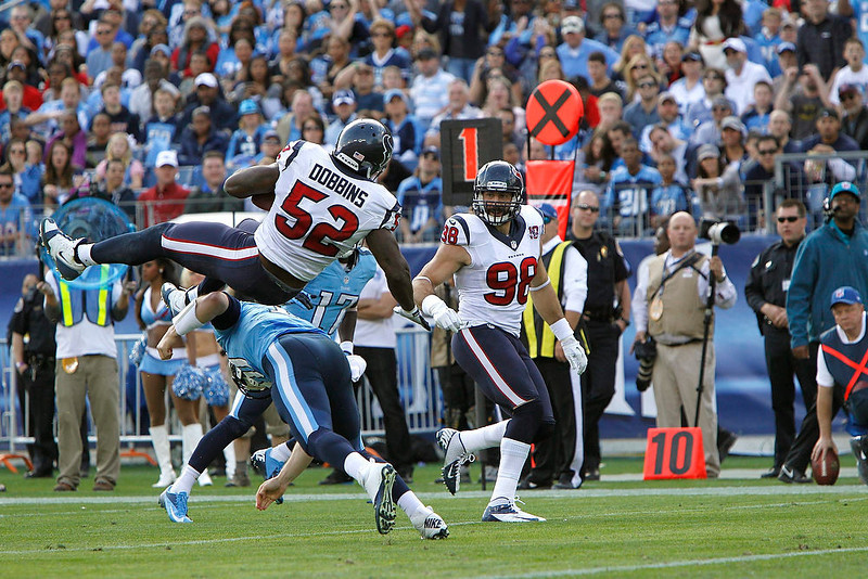 . Tennessee Titans\' quarterback Jake Locker (10) tackles Houston Texans\'  linebacker Tim Dobbins (52) after Dobbins intercepted a Locker pass in the first half of their NFL football game in Nashville, Tennessee December 2, 2012.     REUTERS/Harrison McClary