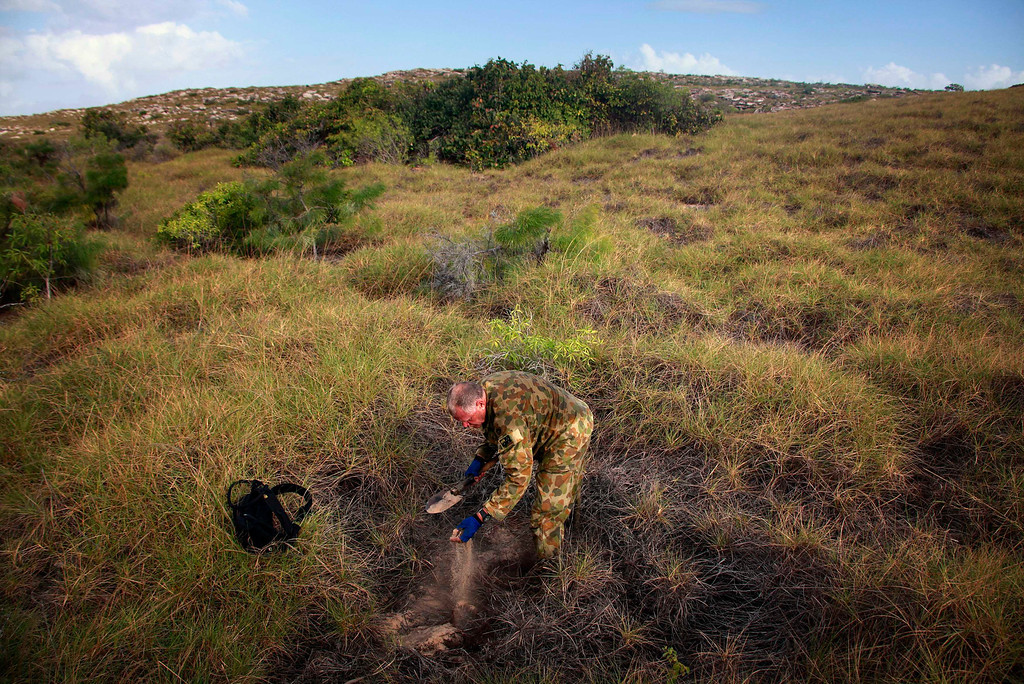 . Patrol Commander Andrew \'Dusty\' Miller of Australia\'s North West Mobile Force (NORFORCE) unit, digs for water amongst spinifex grass on Wigram Island, part of the English Company Islands, located inside Arnhem Land in the Northern Territory July 18, 2013. NORFORCE is a surveillance unit that employs ancient Aboriginal skills to help in the seemingly impossible task of patrolling the country\'s vast northwest coast. NORFORCE\'s area of operations is about 1.8 million square km (700,000 square miles), covering the Northern Territory and the north of Western Australia. Aboriginal reservists make up a large proportion of the 600-strong unit, and bring to bear their knowledge of the land and the food it can provide. Fish, shellfish, turtle eggs and even insects supplement rations during the patrol, which is on the lookout for illegal foreign fishing vessels and drug smugglers, as well as people smugglers from neighboring Indonesia.  Picture taken July 18, 2013. REUTERS/David Gray