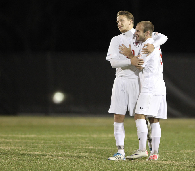 Teammates embrace each other in joy of making the penalty kick.