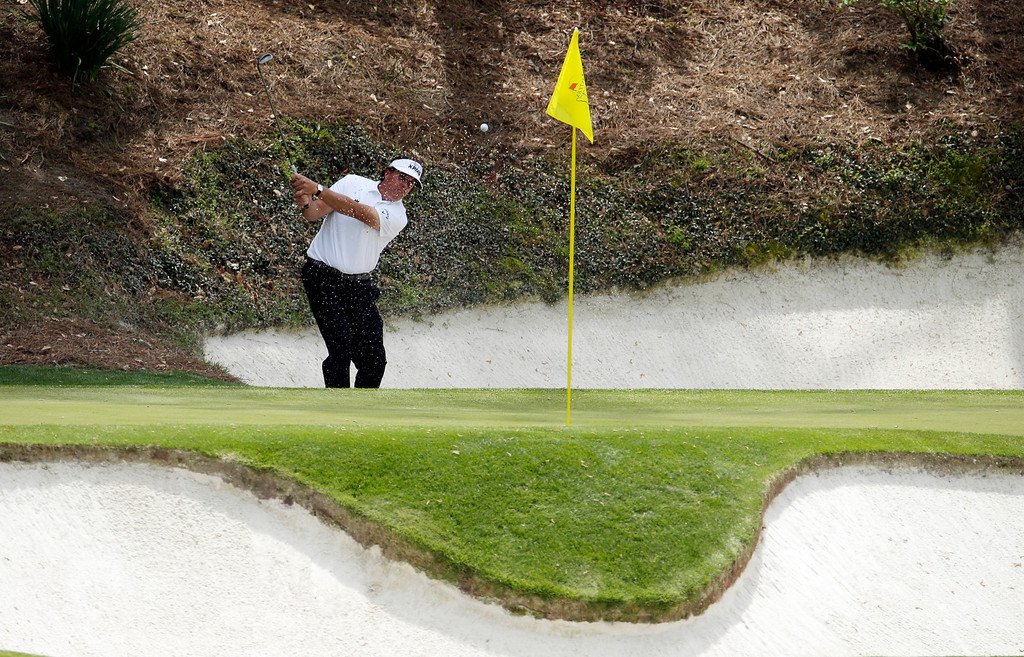 . Phil Mickelson hits out of a bunker on the 12th hole during the second round of the Masters golf tournament Friday, April 11, 2014, in Augusta, Ga. (AP Photo/Charlie Riedel)