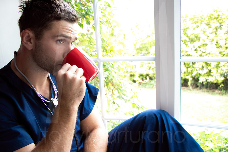 Handsome doctor or male nurse on break looking out of window
