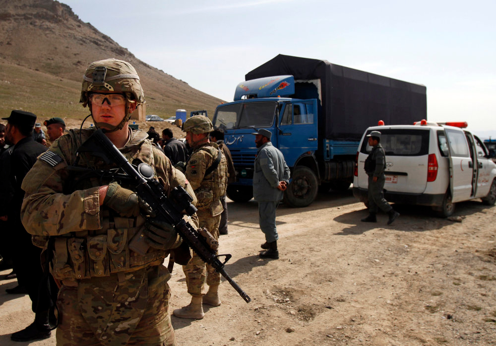 . A U.S. soldier secures the scene after U.S. forces shot on an Afghan truck, center, killing two passengers and injuring another on the road between Kabul and Bagram, Afghanistan, Monday, March 11, 2013. (AP Photo/Ahmad Jamshid)