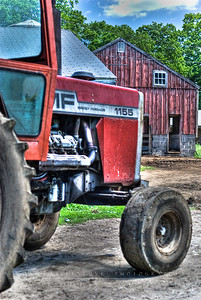 A view of the tractor and the hay barn in the background.