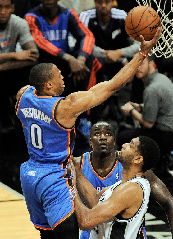. Oklahoma City Thunder guard Russell Westbrook, left, shoots against San Antonio Spurs forward Tim Duncan, right, as Thunder center Kendrick Perkins stands near during the first half of an NBA playoff basketball game on Monday, May 19, 2014, in San Antonio. (AP Photo/Darren Abate)