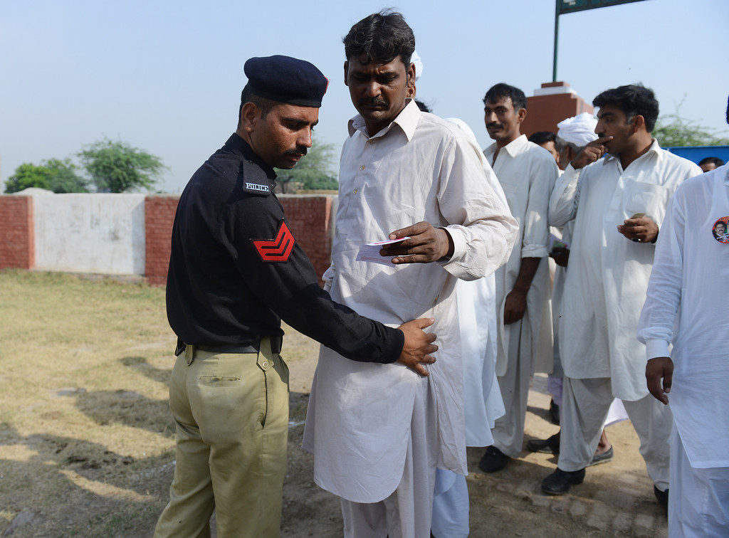 . A Pakistani policeman checks a voter entering a polling station in the village of Dial on the outskirts of Lahore on May 11, 2013.  Bomb attacks wounded 12 people outside polling stations in northwest Pakistan, police said, but many voters were not deterred from casting their ballots in landmark polls. The vote marks the first time that an elected civilian administration has completed a full term and handed power to another through the ballot box in a country where there have been three military coups and four military rulers.  More than 86 million people are eligible to vote for the 342-member national assembly and four provincial assemblies in Khyber Pakhtunkhwa, Punjab, Sindh and Baluchistan. ROBERTO SCHMIDT/AFP/Getty Images