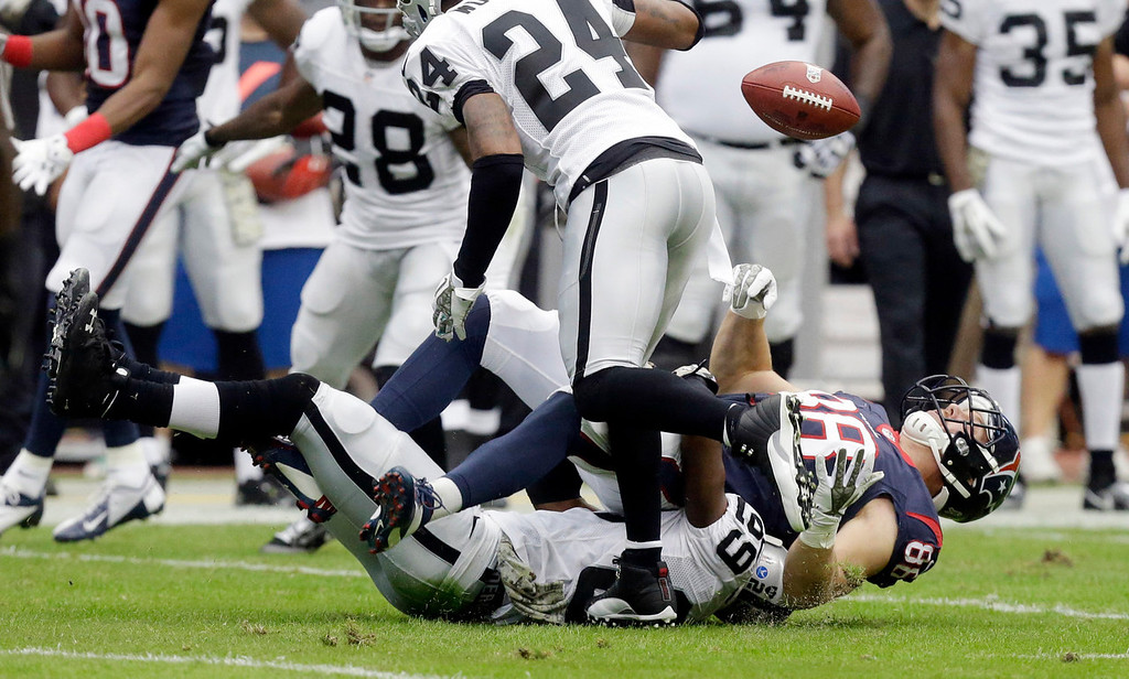 . Houston Texans\' Garrett Graham (88) fumbles as he is hit by Oakland Raiders\' Lamarr Houston during the first half of an NFL football game Sunday, Nov. 17, 2013, in Houston. The Raiders recovered the fumble. (AP Photo/Patric Schneider)