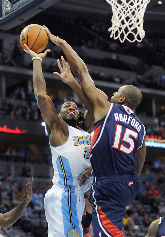 . Atlanta forward Al Horford came across to reject an attempt by Denver forward Kenneth Faried in the first half.  Photo By Karl Gehring/The Denver Post
