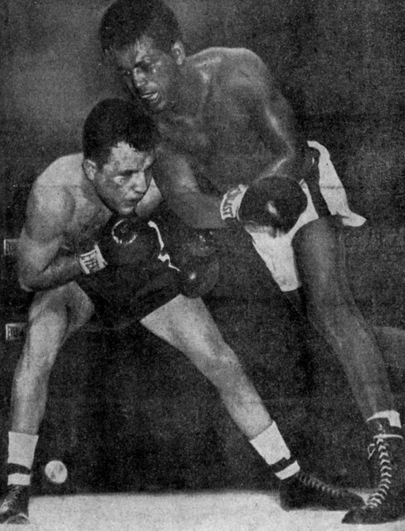 . Missing a terrific swing in the 10th, Sugar Ray Robinson, right, pitches off balance, his shoulder crashing against the crouching Jake LaMotta\'s head, in Chicago, Ill., Feb. 14, 1951. (Ap Photo)