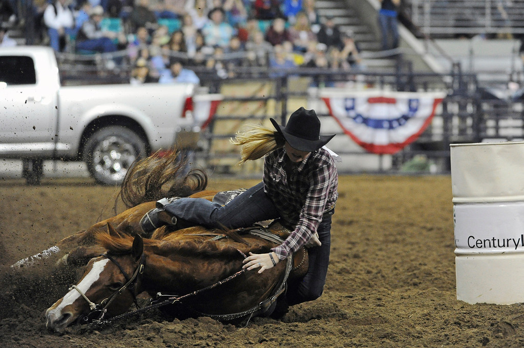 . DENVER, CO- JANUARY 27:  Jessi Eagleberger, of Stringtown, Oklahoma, goes down around a barrel during the barrel race.   The final day of the 2013 National Western Stock show was Sunday, January 27th.  One of the big events for the day was the PRCA Pro Rodeo finals in the Coliseum.  The event featured bareback riding, steer wrestling, team roping, saddle bronc riding, tie down roping, barrel racing and bull riding.  (Photo By Helen H. Richardson/ The Denver Post)
