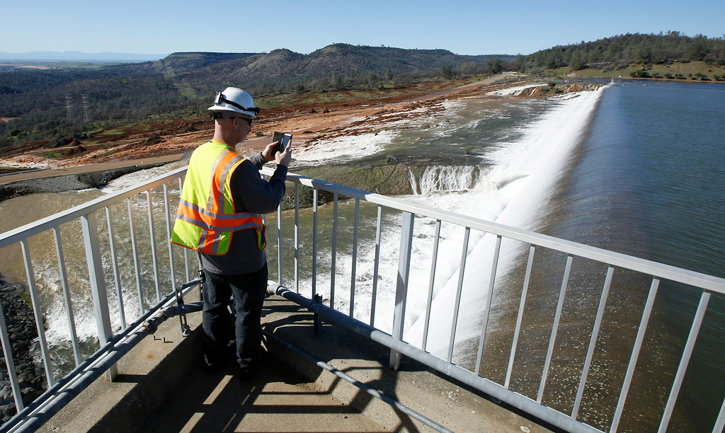 . Jason Newton, of the Department of Water Resources, takes a picture of water going over the emergency spillway at Oroville Dam Saturday, Feb. 11, 2017, in Oroville, Calif. Water started flowing over the emergency spillway at the nation\'s tallest dam for the first time Saturday after erosion damaged the Northern California dam\'s main spillway. (AP Photo/Rich Pedroncelli)