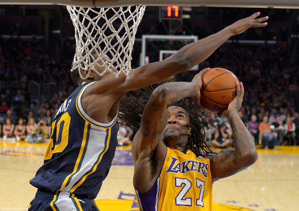 . Los Angeles Lakers center Jordan Hill, right, looks to shoot as Utah Jazz forward Jeremy Evans defends during the first half of an NBA basketball game, Friday, Jan. 3, 2014, in Los Angeles. (AP Photo/Mark J. Terrill)