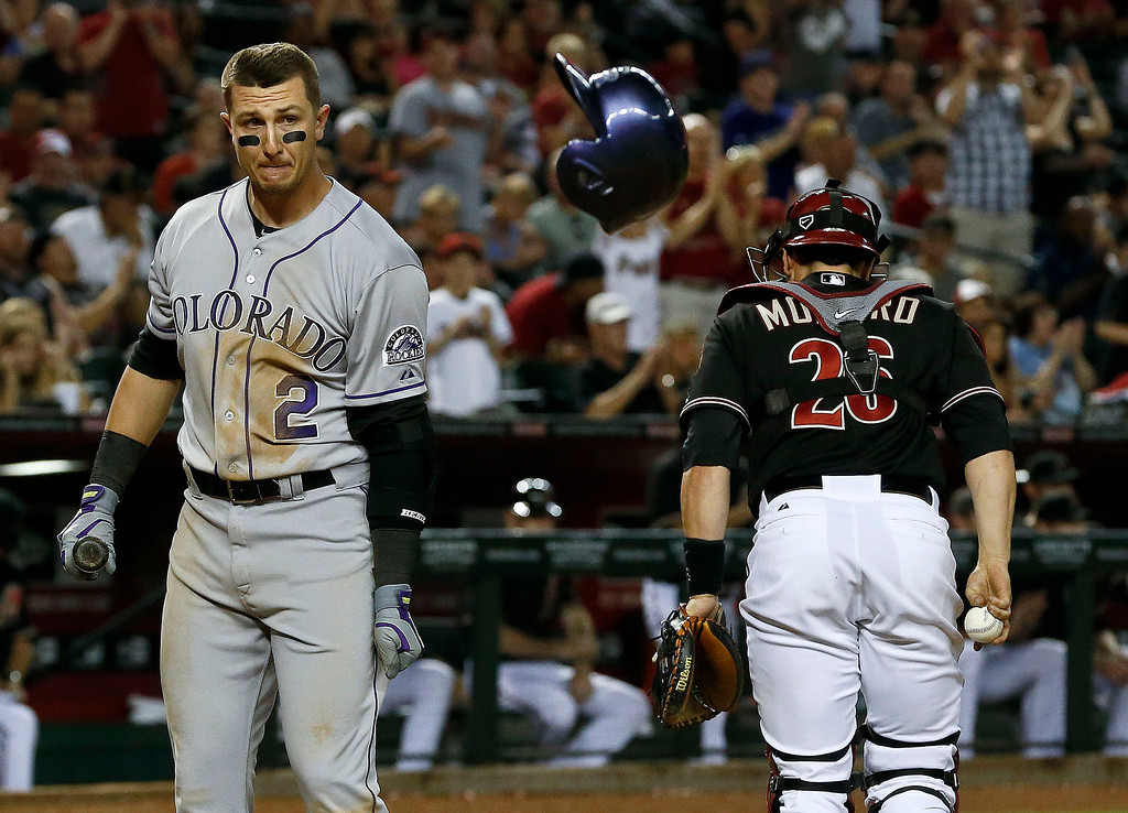 . Colorado Rockies\' Troy Tulowitzki (2) throws his helmet away in frustration after striking out as Arizona Diamondbacks\' Miguel Montero (26) heads back to the dugout in the 10th inning during a baseball game, on Saturday, April 27, 2013, in Phoenix.  The Diamondbacks defeated the Rockies 3-2. (AP Photo/Ross D. Franklin)