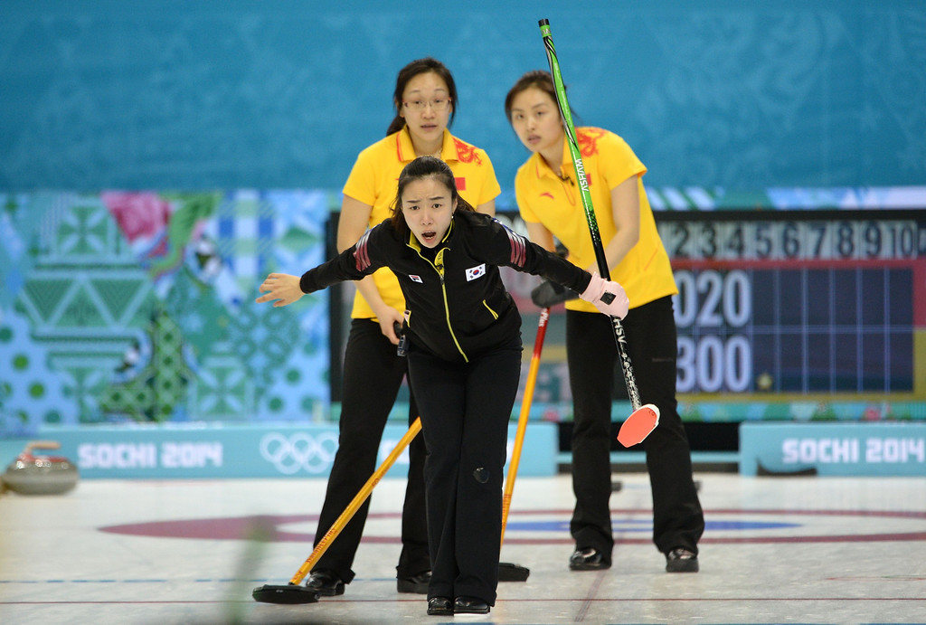 . South Korea\'s Kim Ji-Sun (C) shouts directions after releasing the stone during the Women\'s Curling Round Robin Session 7 against China at the Ice Cube Curling Center during the Sochi Winter Olympics in Sochi on February 14, 2014. JUNG YEON-JE/AFP/Getty Images