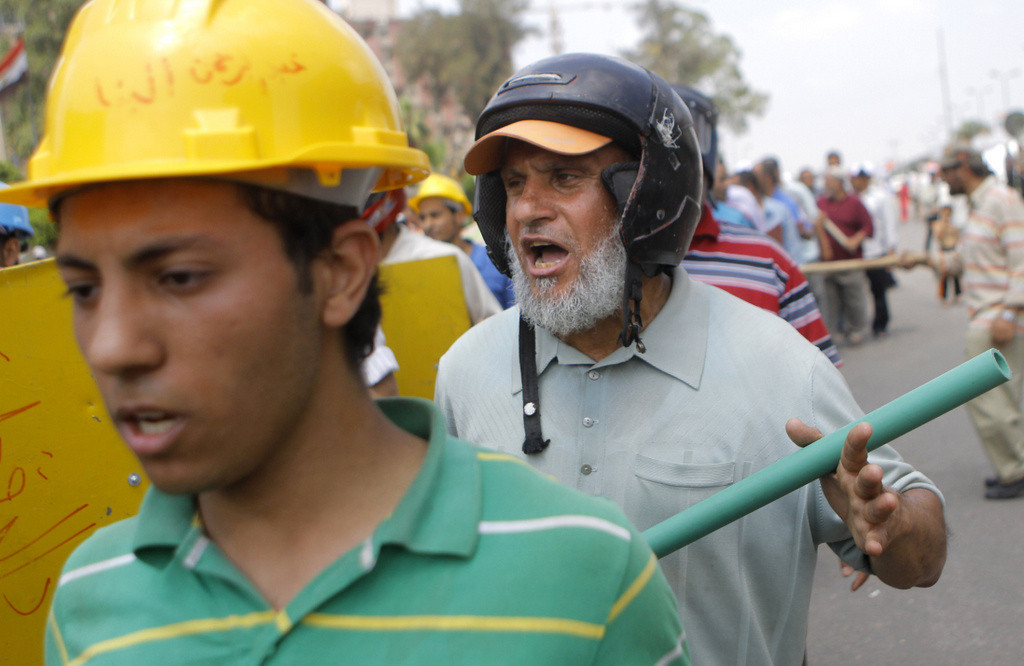 . Sayed Saafan, 57, right, an Egyptian supporter of Egypt\'s Islamist President Mohammed Morsi, holds stick and wears protective gear during training outside of the Rabia el-Adawiya mosque near the presidential palace, in Cairo, Egypt, Tuesday, July 2, 2013. (Associated Press: Amr Nabil)