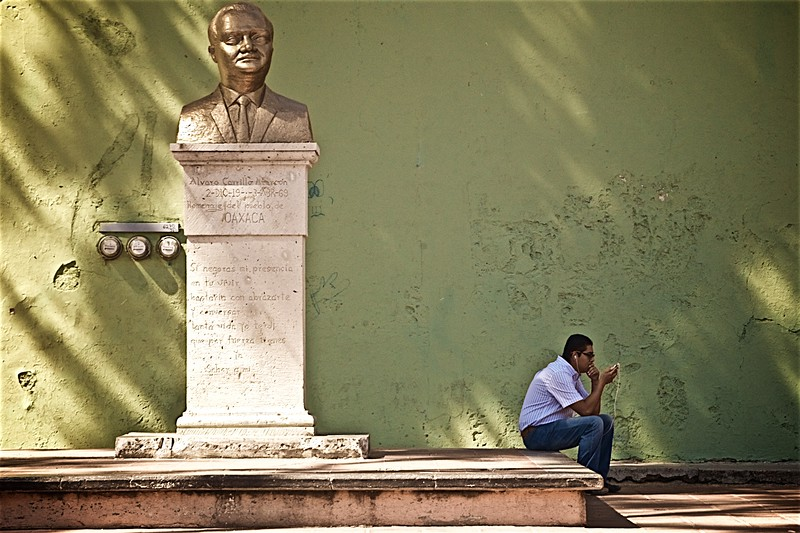 A young man sits listening to his iPod near a bust of Álvaro Carrillo Alarcón in Oaxaca, Mexico.