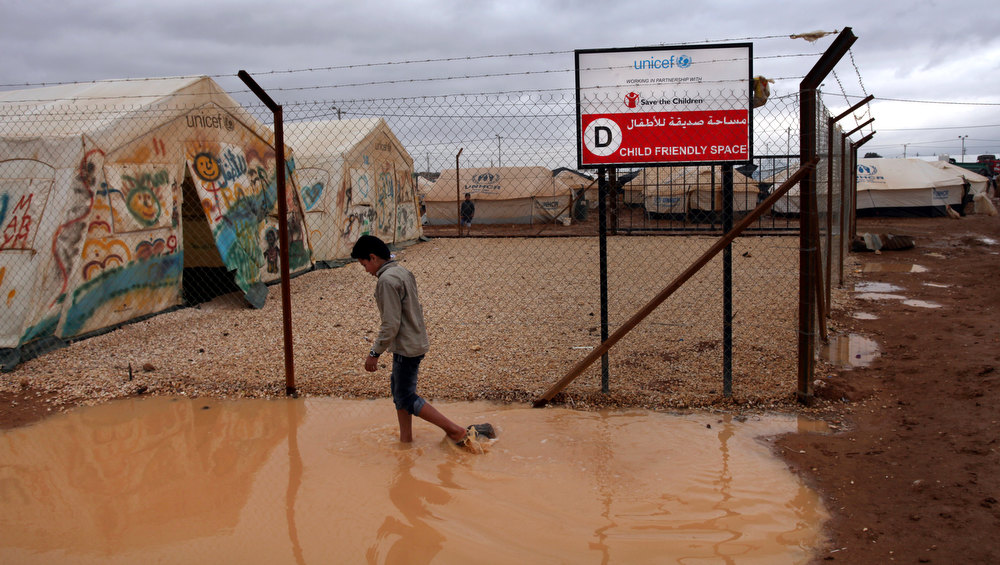 Description of . A Syrian refugee boy makes his way through water and mud, next to a UNICEF school at Zaatari Syrian refugee camp, near the Syrian border in Mafraq, Jordan, Tuesday, Jan. 8, 2013. Syrian refugees in a Jordanian camp attacked aid workers with sticks and stones on Tuesday, frustrated after cold, howling winds swept away their tents and torrential rains flooded muddy streets overnight. Police said seven aid workers were injured. (AP Photo/Mohammad Hannon)
