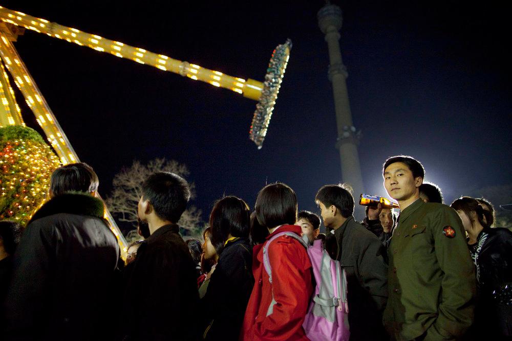 Description of . North Koreans form a line for a ride at an amusement park in central Pyongyang, North Korea on Saturday April 16, 2011.  (AP Photo/David Guttenfelder)