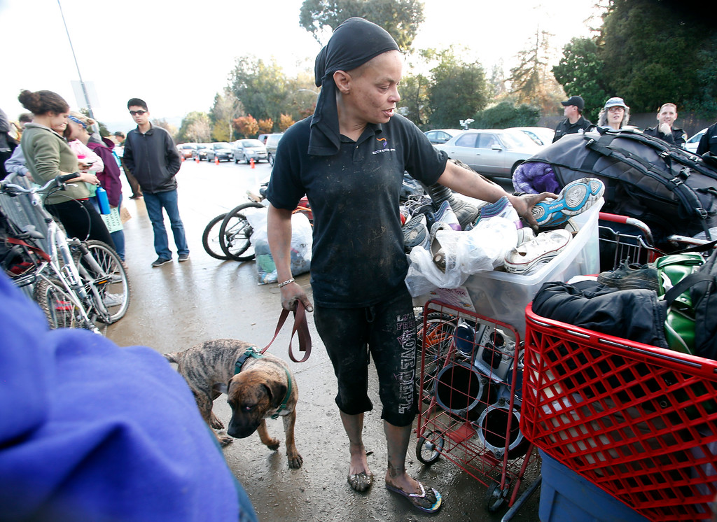 . Toy Larks-Scott, a resident of The Jungle homeless camp, moves her possessions onto Story Road as evictions are served Thursday morning, Dec. 4, 2014, at the site along the Coyote Creek in San Jose, Calif. (Karl Mondon/Bay Area News Group)