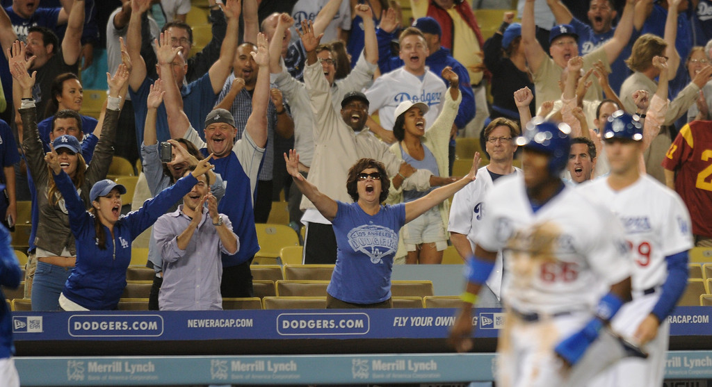 . Fans cheer as Yasiel Puig rounds 3rd base on his way home after being driven in by Adrian Gonzalez in the 12 inning for win. Fans at Dodger Stadium have been treated to a lot of excitement. The Dodgers defeated the New York Mets 5-4 in 12 innings Wednesday night at Dodger Stadium in Los Angeles, CA. 8/13/2013(John McCoy/LA Daily News)