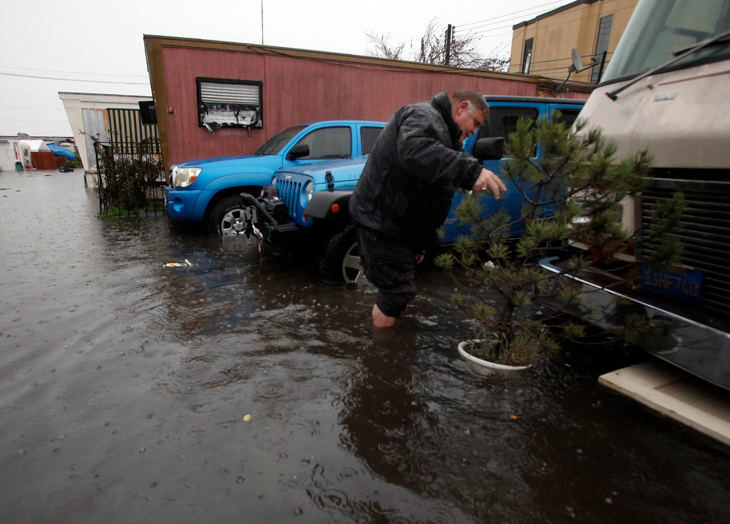 . Mike Aitken, a longtime resident of the Le Mar Trailer Park in Redwood City, Calif., rights a potted pine tree knocked over during Thursday\'s storm, Dec. 11, 2014. (Karl Mondon/Bay Area News Group)