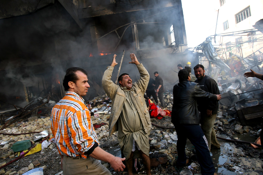 . Iraqis grieve in front of a burning building after a double car bomb attack in central Baghdad, Iraq, Monday, Feb. 12, 2007. Thunderous explosions and dense black smoke swirled through the center of Baghdad when at least one car bomb blew up in an underground parking garage, setting off dozens of secondary explosions and killing at least 59 people, police said. (AP Photo/Khalid Mohammed)
