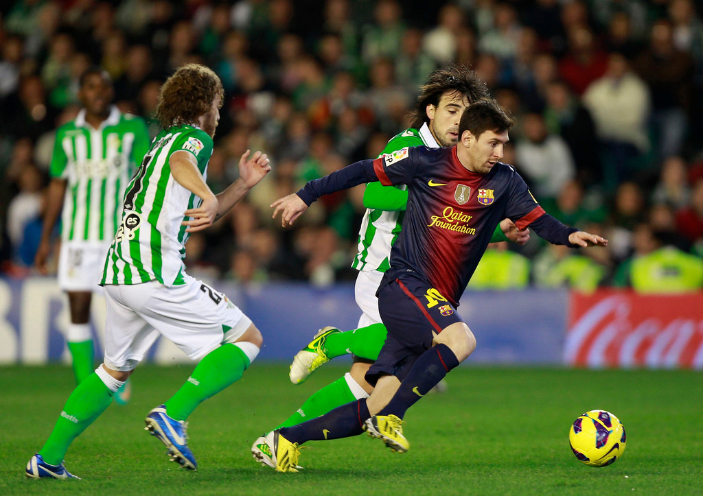 . Barcelona\'s Lionel Messi (R) is challenged by Real Betis\' players during their Spanish First Division soccer match at Benito Villamarin stadium in Seville December 9, 2012. REUTERS/Marcelo del Pozo