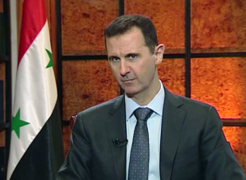 """. President Bashar Assad speaks during an interview. Syria\'s president accused the West on Wednesday of backing al-Qaida in his country\'s civil war, warning it will pay a price \""""in the heart\"""" of Europe and the United States as the terror network becomes emboldened. The rare TV interview comes as the embattled president\'s military is fighting to reverse rebel advances, with a rocket attack killing at least 12 people in a central village on Wednesday. (AP Photo/Syrian State TV via AP video)"""